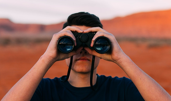 man-with-binoculars-in-desert-searching-for-executives